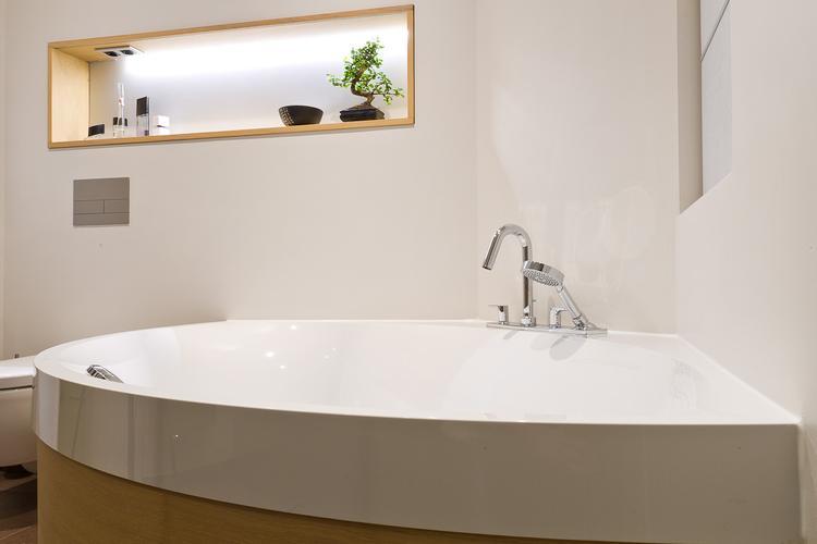 De eerste kamer in deze badkamer staat een luxe hoekbad met een