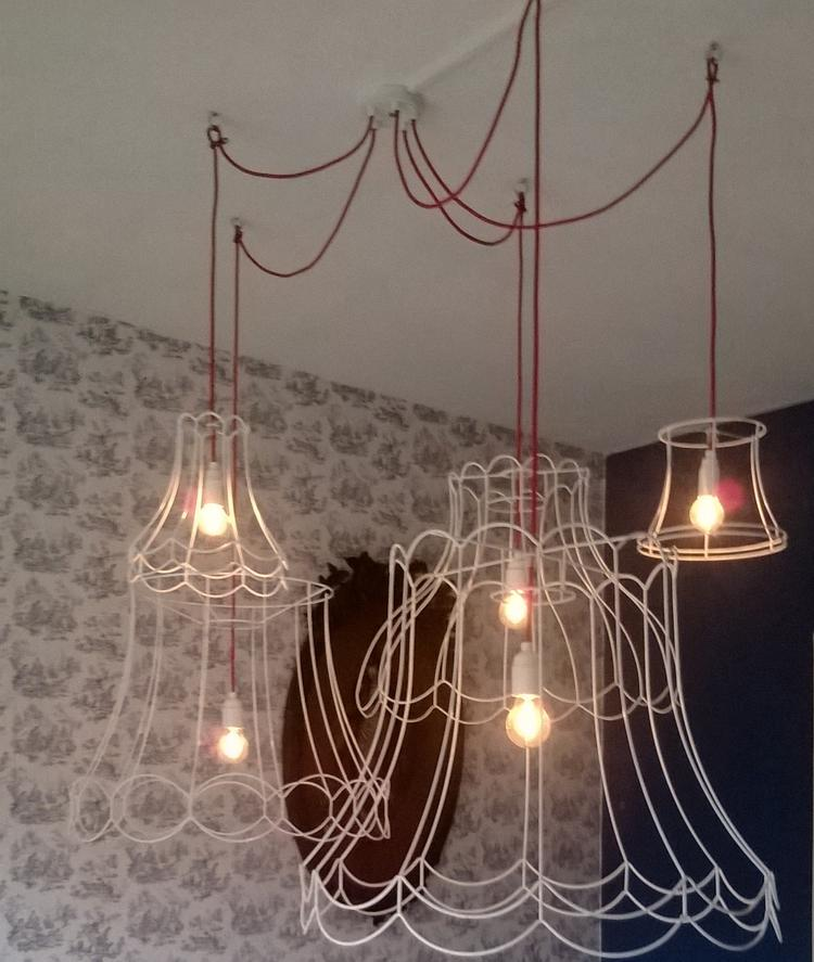 supergave lamp boven eettafel van oude lampenkappen en rood snoer
