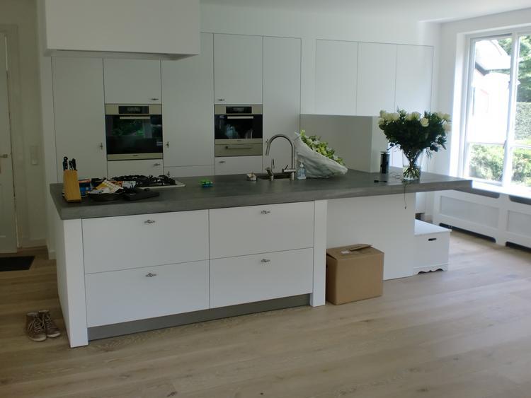 Keuken blad van beton, een witte keuken met mooie grepen en een ...