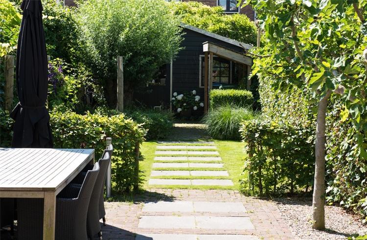 Mooi tegelpad door het gras in de tuin foto geplaatst door