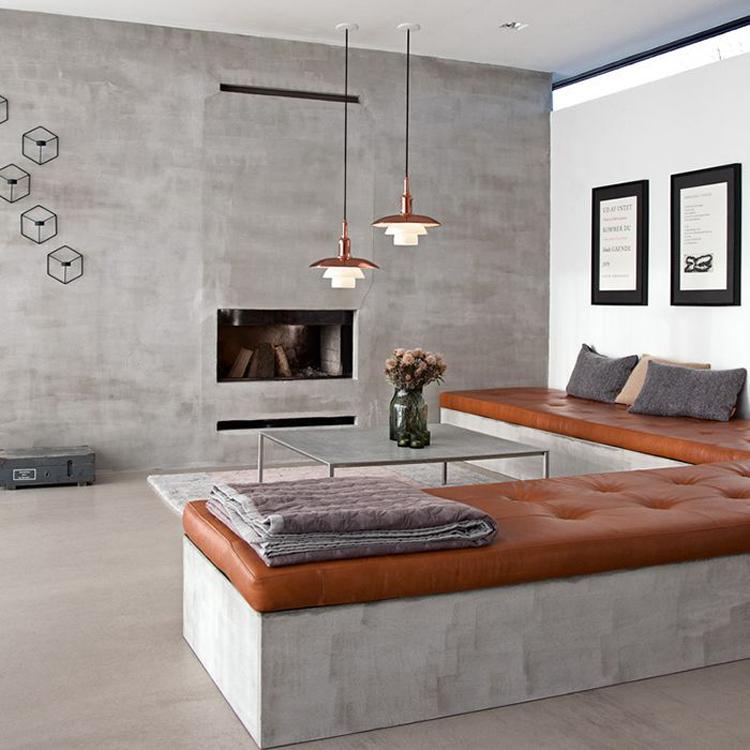 Zeer moderne woonkamer met koperen hanglampen, betonnen banken met ...