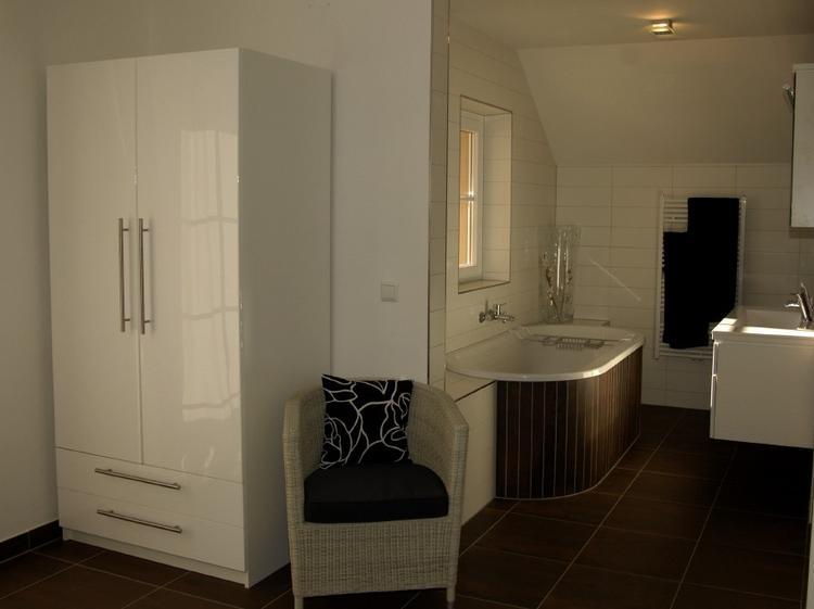 Badkamer in warme tinten rond ligbad mat witte tegels van