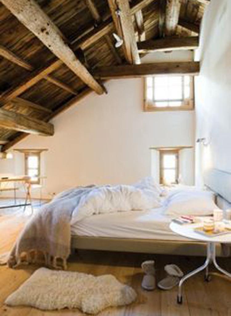 Ruime slaapkamer met stoere houten balken en dakconstructie.. Foto ...