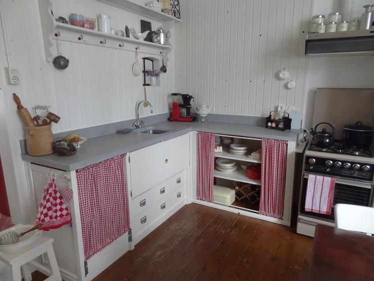 Een keuken met gordijntjes en deurtjes.. foto geplaatst door