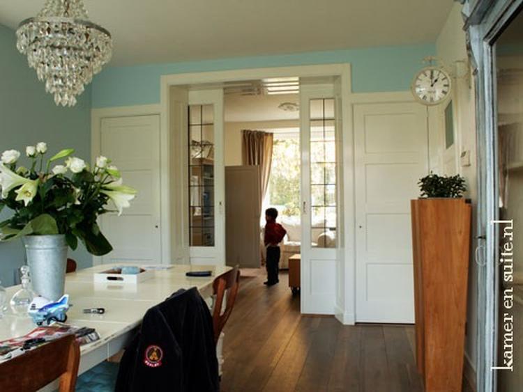 Eetkamer en woonkamer wordt gescheiden door glas in lood ...