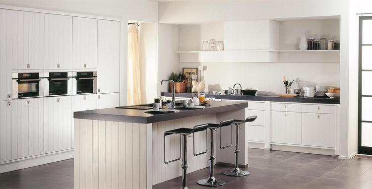 Witte landelijke keuken met ontbijtbar en veel opbergruimte. Dat ...