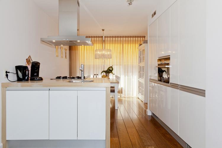Witte keuken met kunststof wangen aan zijkant eiland met ...