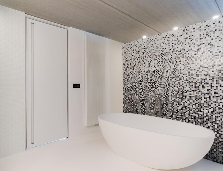 Moderne design binnendeur in een strakke badkamer met mozaïek en een