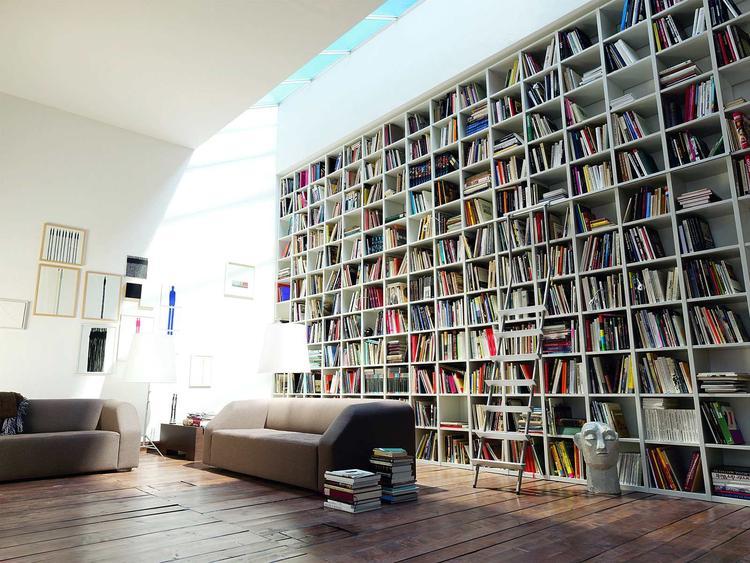 Woonkamer met grote boekenkast met vakjes. Een boekenkast geeft een ...