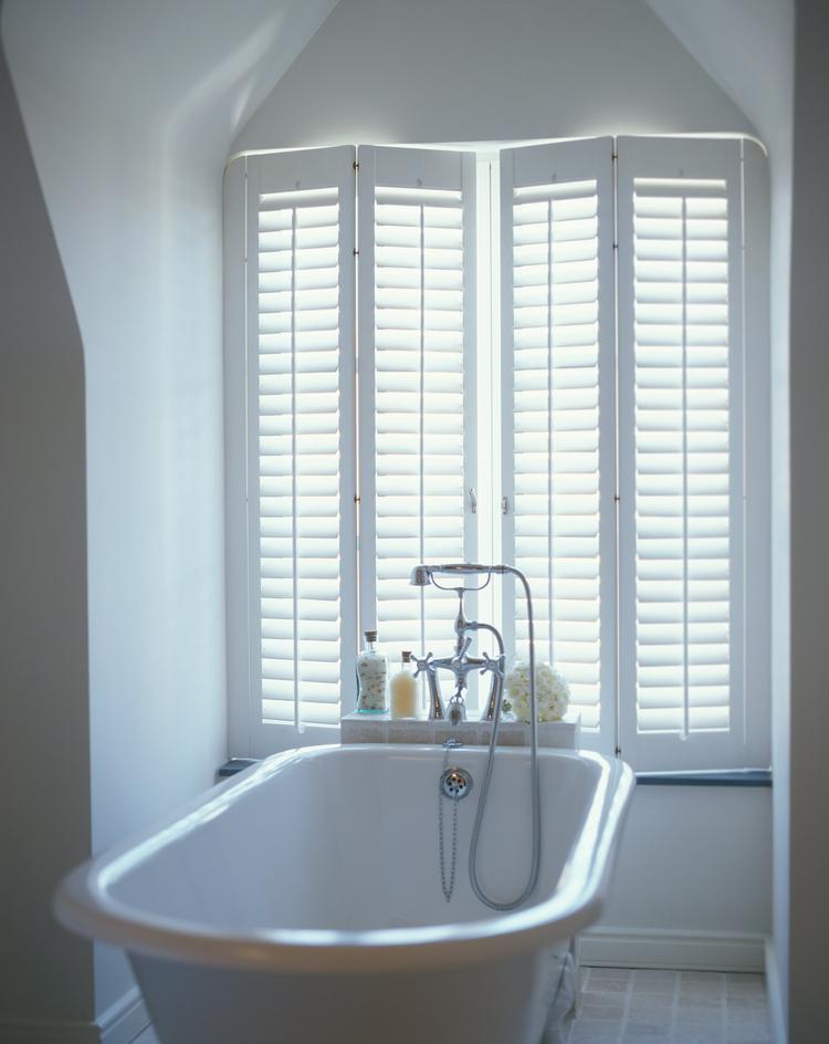 Badkamer met vrijstaand bad en shutters. In een badkamer zijn grote ...