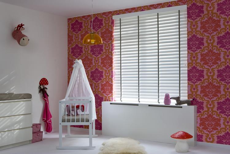 Witte kinderkamer met felgekleurd behang op één muur een