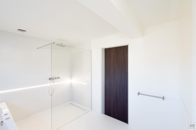 Moderne Witte Badkamer : Moderne wengé binnendeur in een verder witte badkamer met de deur