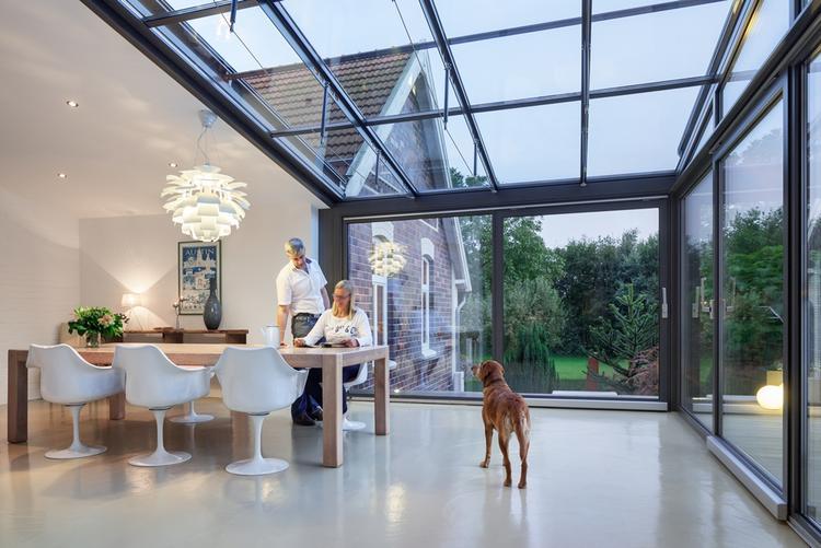 Uitbreiding huis. hous leven rond tuin in een glazen uitbreiding