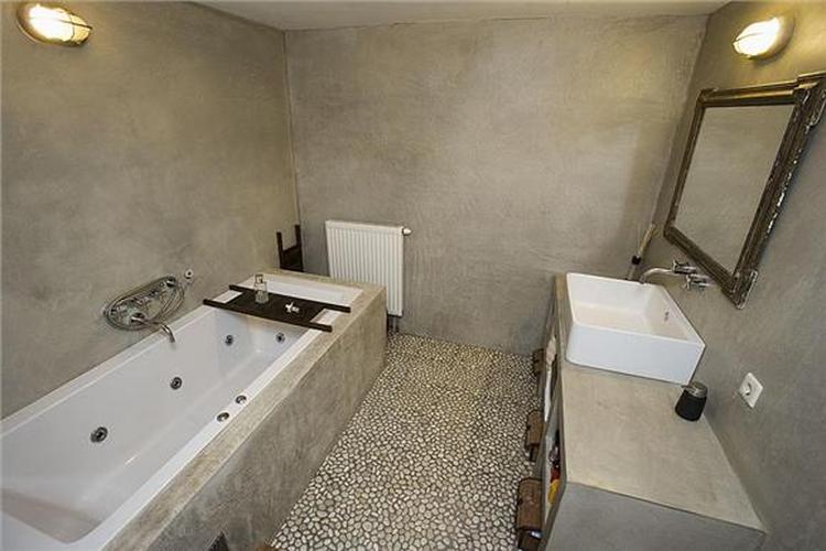 Badkamer met tadelact op de muren en kiezelsteentjes op de vloer ...