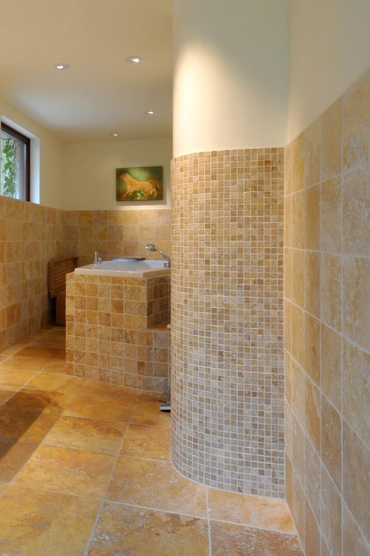 De travertin tegels en mozaiek geven deze badkamer een warme en ...