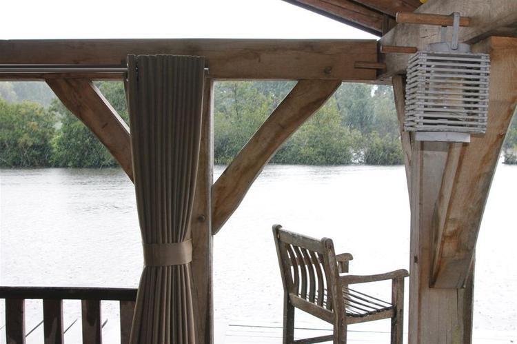 Mooie houten overkapping met speciale buiten gordijnen.. Foto ...