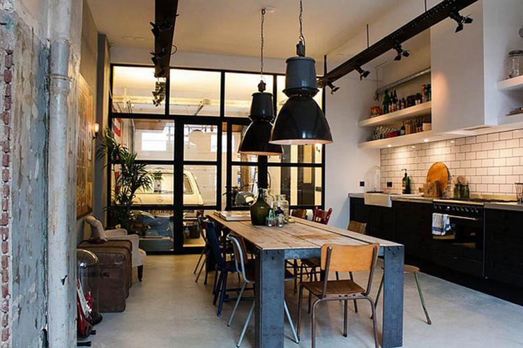 keuken zwarte hanglampen boven een stoere eetkamertafel met
