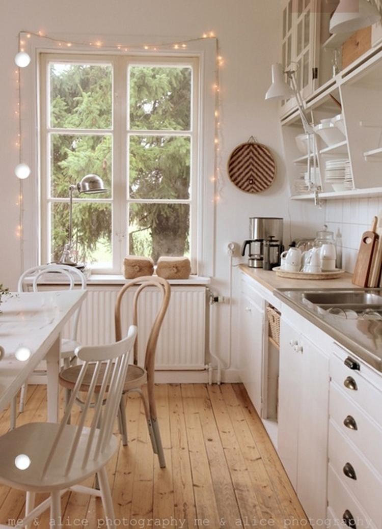 Neutrale witte keuken met houten vloer en gezellige lampjes.. Foto ...