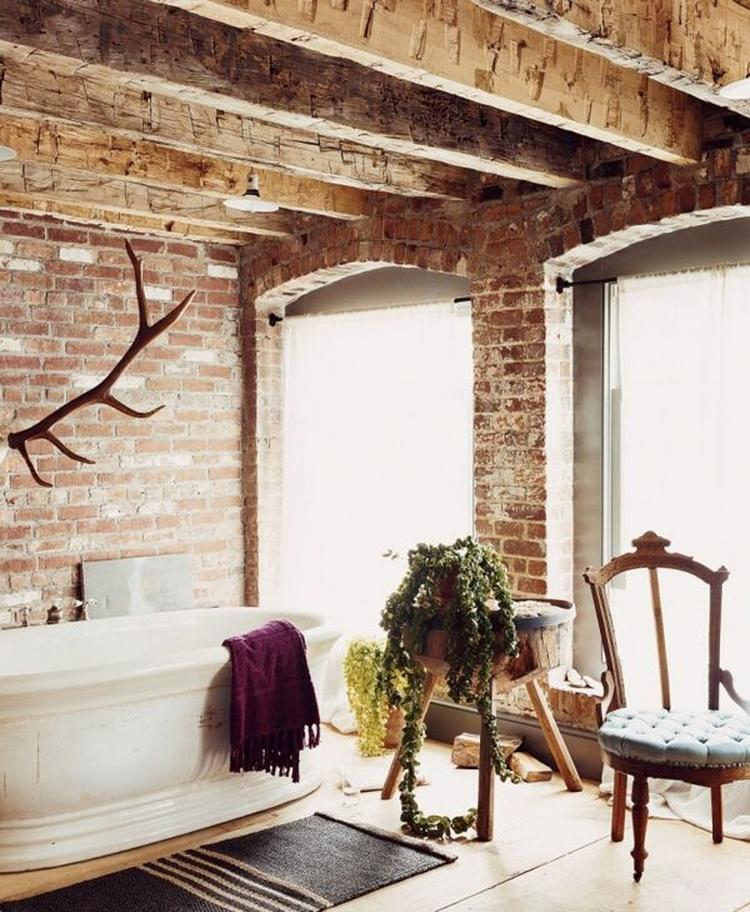 Stoere badkamer met ligbad, houten blaken, gemetselde muur, stoel en ...