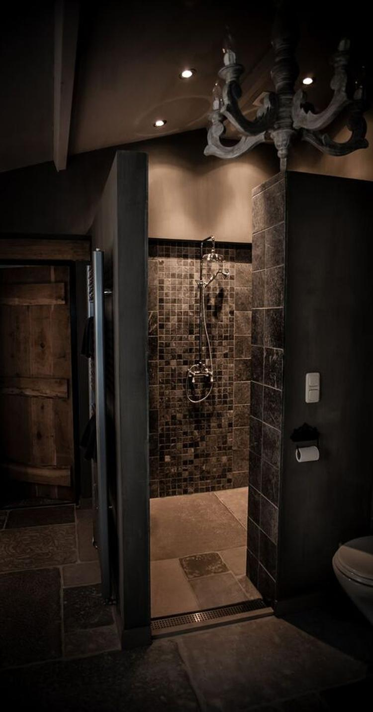 landelijke badkamer met douche grijze tegels en chandelier foto
