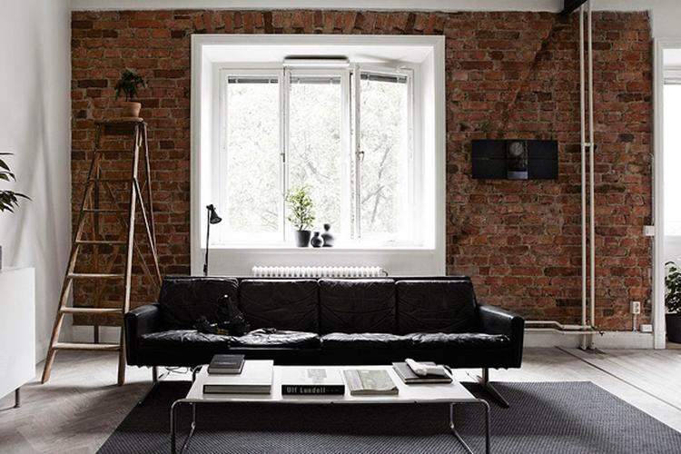 Prachtige zwarte leren bank met een bakstenen muur.. foto geplaatst