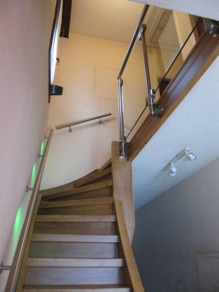 trapleuning met verlichting en een glazen balustrade tegen de ...