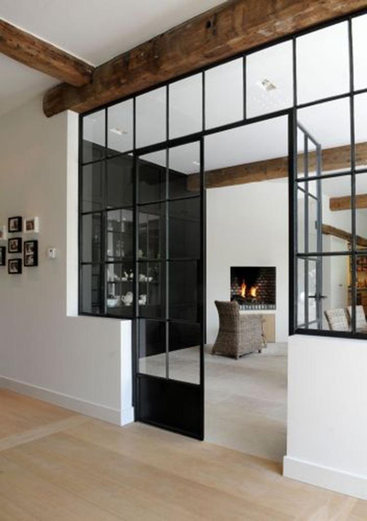 mooie zichtbare houten balken in een modern interieur dankzij de glazen wand worden de ruimtes