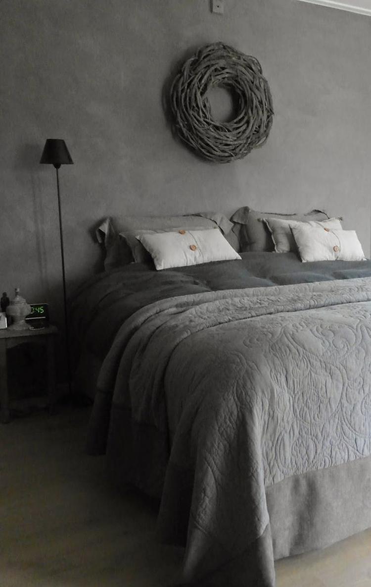 Gezellige landelijke slaapkamer in grijs. Leuke kussens en een sprei ...