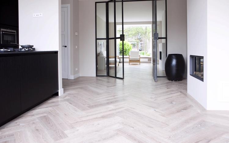 Lichte houten vloer met donkere keuken, hoge plint en stalen ...