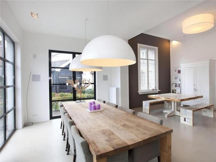 Ruime eetkamer met zwarte puien, houten eettafel, grijze stoelen en ...