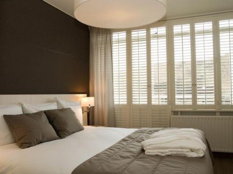 Koffie- en zandtinten geven een slaapkamer rust en warmte. Foto ...
