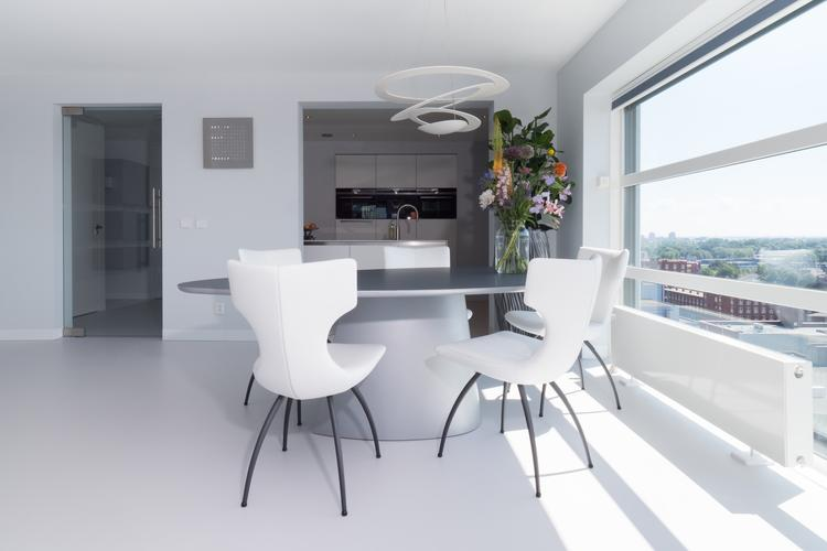 Kunststof gietvloer in stijlvol ingerichte moderne eetkamer. foto