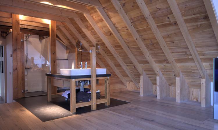 badkamer op zolder. Ruime, rustieke badkamer van hout, steen en glas ...