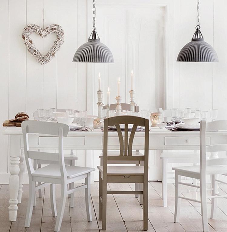 Gezellige witte eetkamer met verschillende stoelen en mooie lampen ...