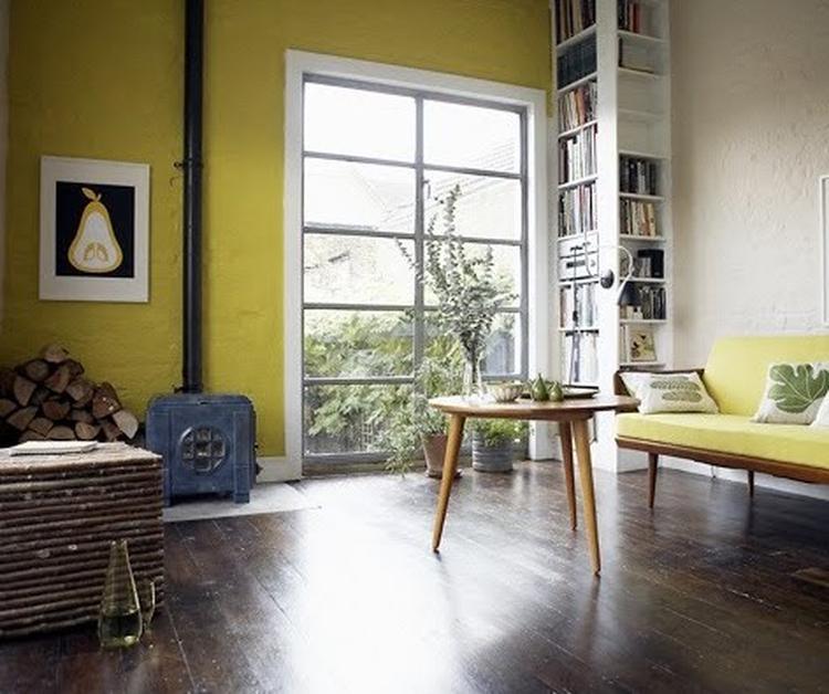 Woonkamer met gele muur en donker houten vloer. Foto geplaatst ...