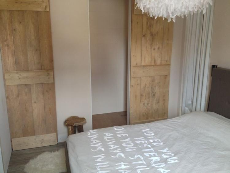 onze slaapkamet met steigerhouten schuifdeuren naar badkamer en kast