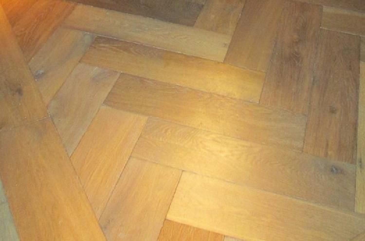 Brede houten planken visgraat vloer. foto geplaatst door