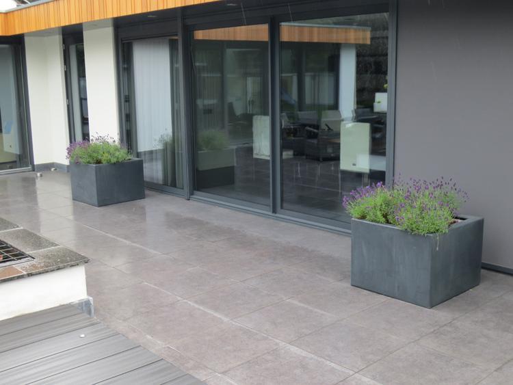 Minimalistisch vormgegeven tuin bij een modern gerenoveerde woning