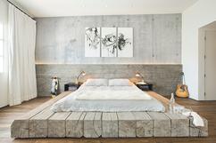 stijlvolle slaapkamer met heel bijzonder bed het matras ligt op een groot plateau van
