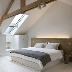 mooi contrast tussen strakke witte muren en houten balken in de slaapkamer