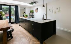 Stijlvolle keuken met zwart hout visgraat vloer en betonlook