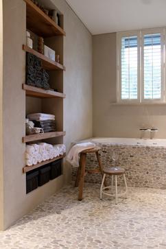 wat een leuke badkamer met die kiezels en shutters